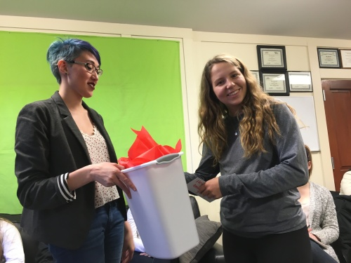 Design Editor Rebekah Markillie awards new Creative Director Hannah Baade a trash can for reasons only they understand.