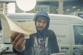 Budhat serves a hotdog at his Times Square Halal cart. While the carts seem to blend together, each one is worked by a unique individual with their own life experiences. Connor Lorber, University of Portland (Nancy Copic); lorberconnor@gmail.com